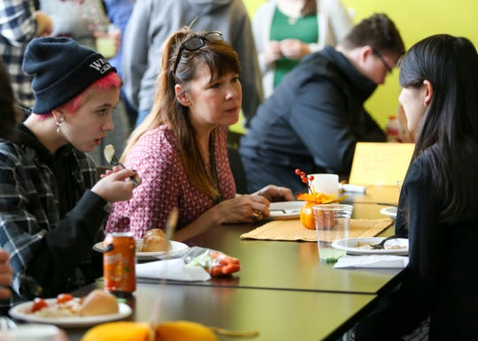 Barker Creek Community School teacher Lindi Zuber chats with students Alexa Pelegri, right, and Ciara King, left, during a home-cooked lunch for the students and staff at the alternative school.
