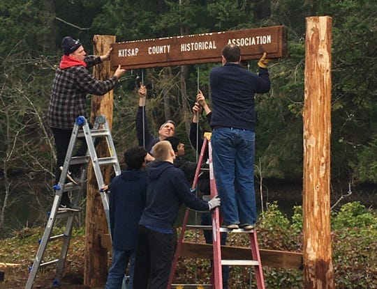 Scouts and volunteers help erect a sign that pays tribute to an old mill in Seabeck on Saturday.