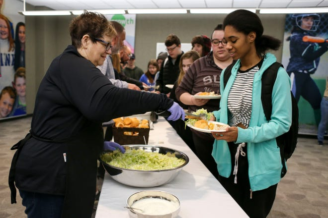 Lali Simpson, junior at Barker Creek Community School, gets salad plopped onto her plate next to rolls and gravy mashed potatoes before the Thanksgiving meal.