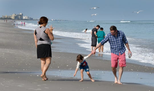 Tourists walk along the beach across from the Fifth Avenue Boardwalk in Indialantic. Mini Kang and Christopher Roach were visiting from California to see relatives for Thanksgiving. They are with their children, baby Jojo, in a baby carrier Kang is holding; and daughter Ellie.