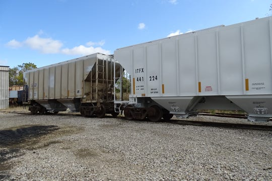 Two cars sit in the yard at Bucyrus Railcar Repair -- one before painting, left, and the other, after.