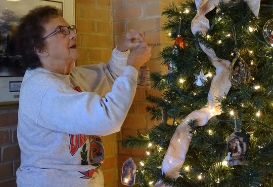 Maxine Brown hangs an ornament on a tree in the narthex of Good Hope Lutheran Church. The church will be one of the stops on the Bucyrus Tourism and Visitors Bureau's Christmas Tour.