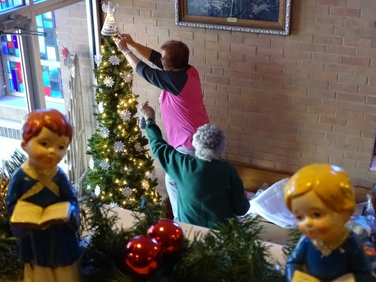 Julia Schreffler and Virginia Meister, from left, decorate a tree in the entryway of Good Hope Lutheran Church.