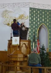Tom Etsinger and Mike Zahn, from left, hang an angel decoration in the sanctuary of Good Hope Lutheran Church as Rod Streib, seated, watches.