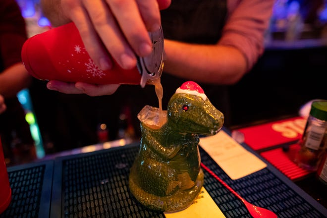 A bartender pours a drink in a Christmas themed mug at Miracle Cocktail Pop-Up Christmas bar at Katz 21. It will be open from Nov. 25 until Dec. 31 and features Christmas themed decor and cocktails.