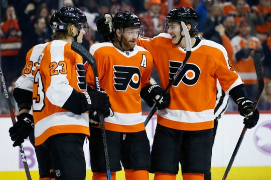 Philadelphia Flyers' Sean Couturier (14) celebrates with Philippe Myers (5) and Oskar Lindblom (23) after scoring a goal during the second period of an NHL hockey game against the Vancouver Canucks, Monday, Nov. 25, 2019, in Philadelphia. (AP Photo/Matt Slocum)