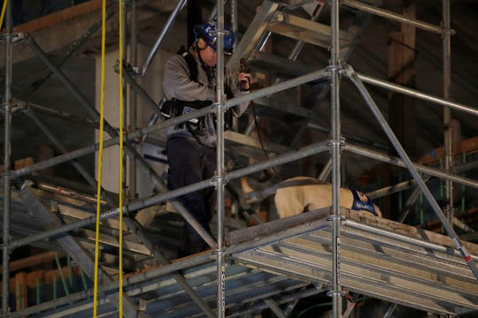 Search and rescue dogs are brought into the scene of a partial building collapse at the construction site on W. 4th Street between Race and Elm Streets in downtown Cincinnati on Tuesday, Nov. 26, 2019. Turner Construction announced that four injured workers were released from the hospital late Monday night, but search and rescue crews worked through the night in search of one missing worker.