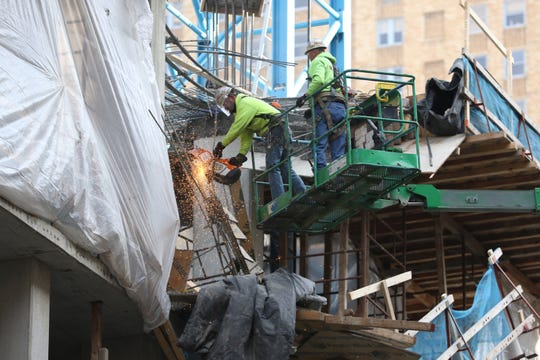 Construction workers remove debris from a partially collapsed building to prepare for high winds on Tuesday, Nov. 26, 2019, on the 100 block of W. 4th Street. The building partially collapsed on Monday, one worker is missing on site.