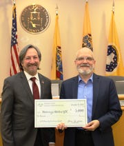 Somerset County Freeholder Director Brian D. Levine (left)presents a ceremonial check to the Rev. Timothy J. Wolf, who chairs the Hillsborough/Millstone Municipal Youth Services Commission.