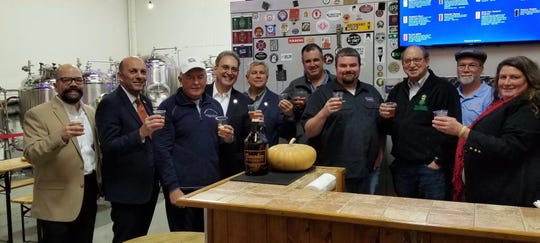 """Raising toast to the pumpkin beer collaboration between Flounder Brewing and Norz Hill farm are Hillsborough Business Advocate David Kois; Hillsborough Mayor Frank DelCore: Assemblyman Eric J. Houghtaling; Assemblyman Roy Freiman; State Sen. Kip Bateman; Rich Norz, owner of Norz Hill Farm;  Jeremy """"Flounder"""" Lees, owner of Flounder Brewing; New Jersey Secretary of Agriculture Doug Fisher; Doug Duschl , head brewer of Flounder Brewing; Debbie Norz. owner  of Norz Hill Farm and member of  New Jersey State Board of Agriculture."""