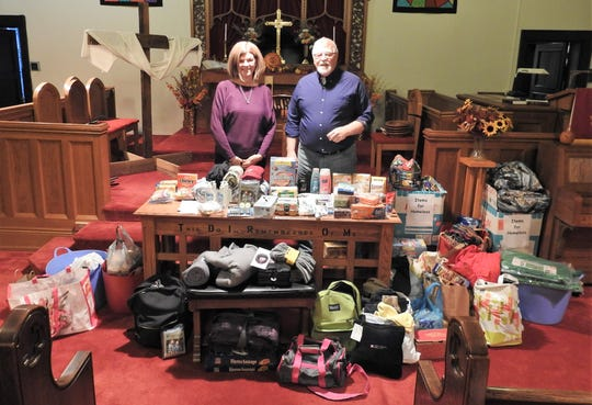 Kathy Robbins and Joe Sanders of Standing Oaks of East Central Ohio and the Coshoton County Homeless Coalition with a sampling of items collected to help the homeless in the community. A temporary homeless shelter, with workers needed, is in the works for January and February.