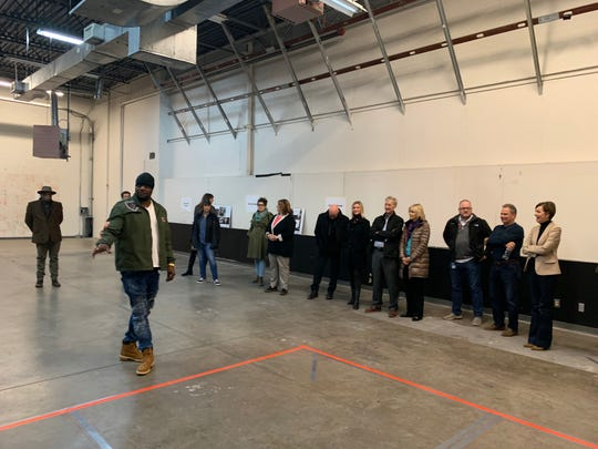 "Will Keeps addresses a crowd Friday, Nov. 22, 2019, in the open space of his new facility for ""Starts Right Here,"" 455 SW Fifth St. Iowa Gov. Kim Reynolds, far right, showed her support by attending a preview of the building's planned services. Keeps started the nonprofit to serve at-risk metro youths. He plans to fill the pictured space with a recording studio, weight room and lounge area, among other attractions for teens."
