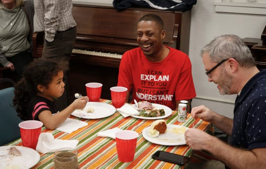 Eric Harris of Iowa City, center, shares a laugh with family and friends during a Thanksgiving dinner for ex-convicts and their families on Nov. 21 at the One Ancient Church in Iowa City. Harris, 40, says his inability to vote makes him feel like less of a citizen.