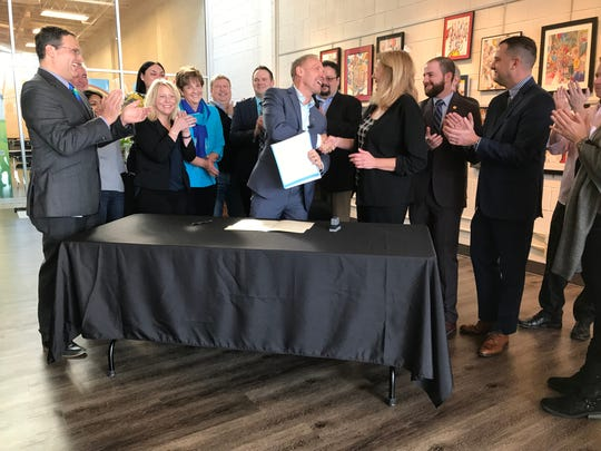 After signing a resolution banning anti-LGBT discrimination in county hiring and firing on Nov. 26, 2019, Oakland County Executive Dave Coulter congratulates County Commissioner Penny Luebs, D-Clawson, who led the initiative.
