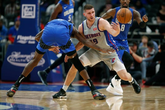 Detroit Pistons guard Svi Mykhailiuk tries to protect the ball from Orlando Magic forward Al-Farouq Aminu during the second half Nov. 25, 2019, in Detroit.