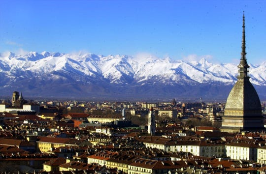 A view of Turin, Italy, with the main city landmark, the Mole Antonelliana, at right, and the Alps in background are seen in this December 2005 photo. (AP Photo/Massimo Pinca)