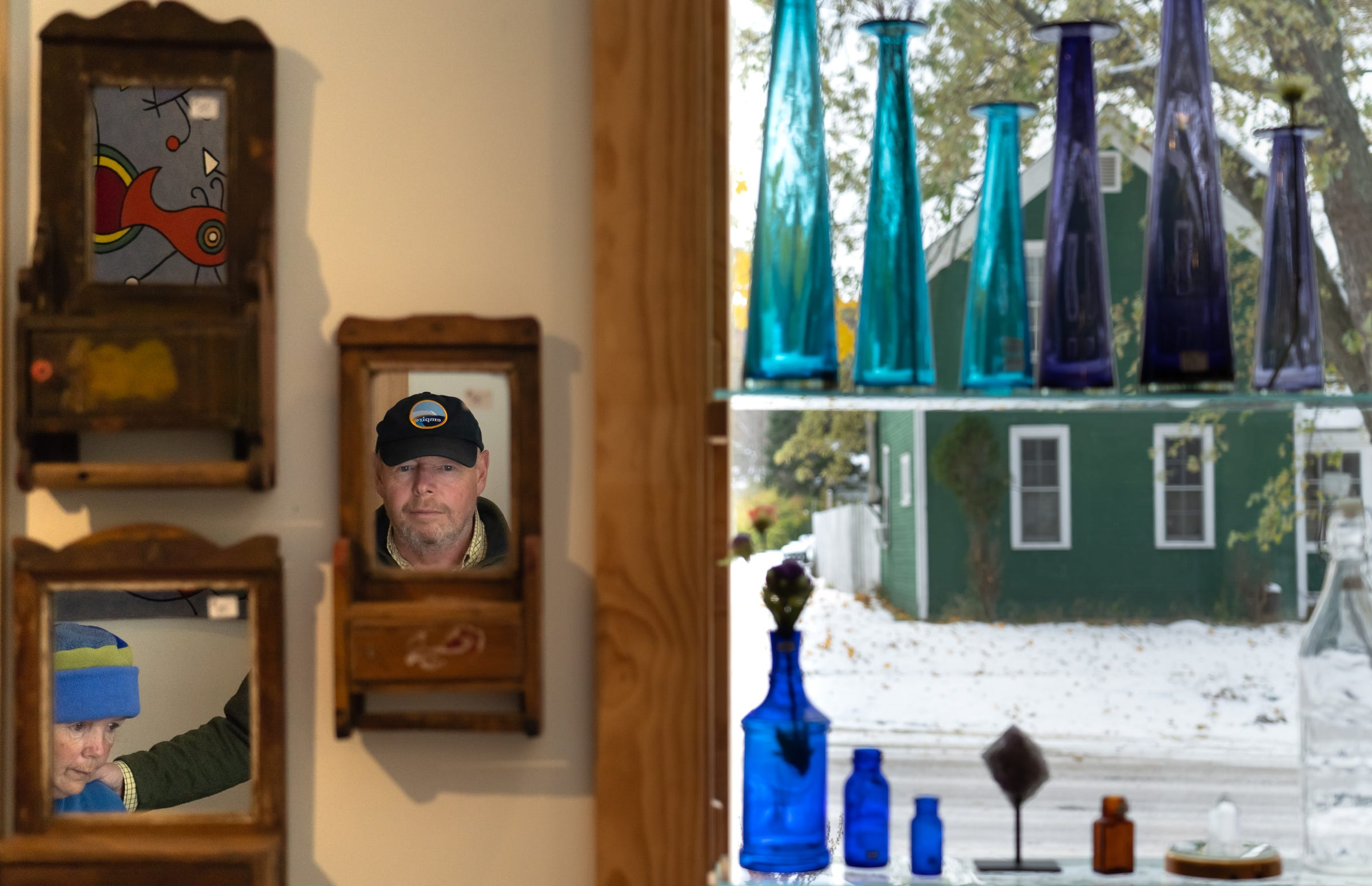 """Paul Skinner is reflected in a mirror as his wife Heidi is reflected in another on Wednesday, Nov. 8, 2019, inside the Miser's Hoard gift shop in downtown Empire. """"It's idyllic,"""" he said of life in Empire. """"If one can find a way of making a living it's very idyllic. It's unique. Like the rest of the county, there's no box stores, there's no fast-food restaurants. It's almost like Mayberry."""""""