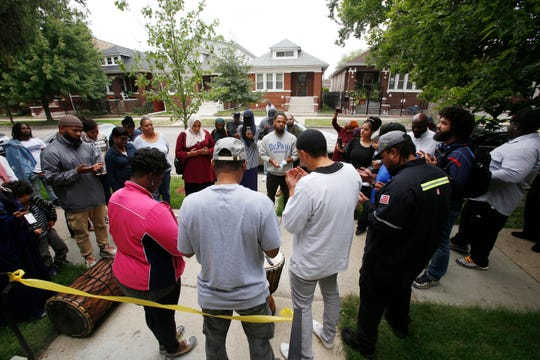 Mary and Hassan Smith, center with backs to camera, pray with well-wishers outside their newly rehabbed home in the Chicago Lawn neighborhood of Chicago on Sept. 6, 2019.