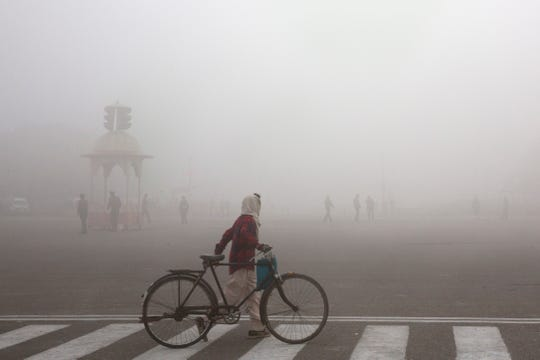 A cyclist amidst morning smog in New Delhi, India.