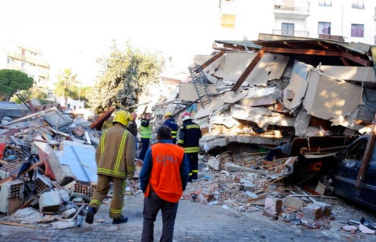 Firefighters stand next to a damaged building after a magnitude 6.4 earthquake in Durres, western Albania, Tuesday, Nov. 26, 2019.