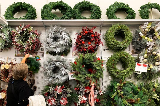 In this Nov. 9, 2019, file photo a woman looks through holiday wreathes on sale at a retail store during in Pembroke Pines, Fla.
