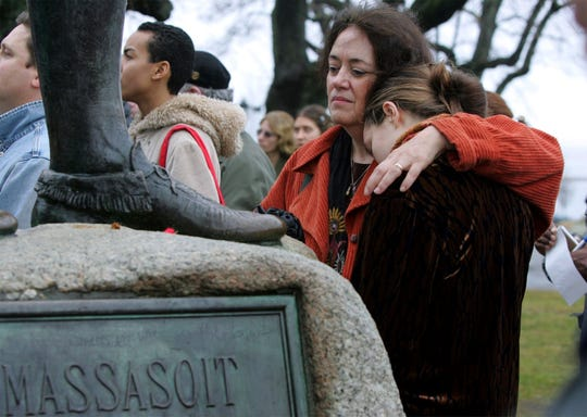 Native American supporter Deborah Theodore, left, of Belmont, Mass., and her daughter, Sofia Theodore-Pierce, stand together in 2004 by the statue of Massasoit on Cole's Hill in Plymouth, Mass., during the 35th National Day of Mourning.