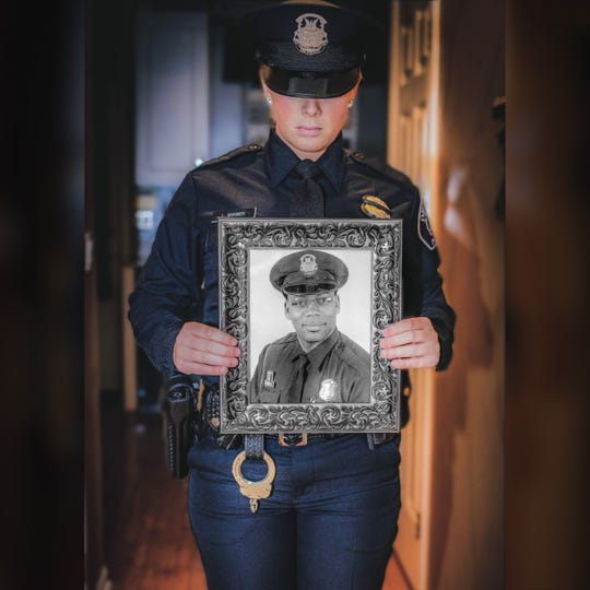 Detroit police officer Linze Shriner with a photo of her partner, Rasheen McClain.