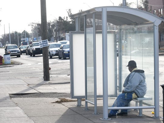 A bus passenger waits at one of the new bus stop shelters at the corner of Livernois and West McNichols in Detroit. Upgrades include solar-powered lighting systems and USB charging ports.