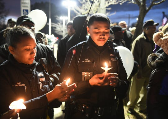 Detroit police officer Devon Leonard, left, relights the candle held by fellow officer Derrick Daniel, right, at a vigil for officer Rasheen McClain at the Detroit Police Department's seventh precinct in Detroit, Monday night.