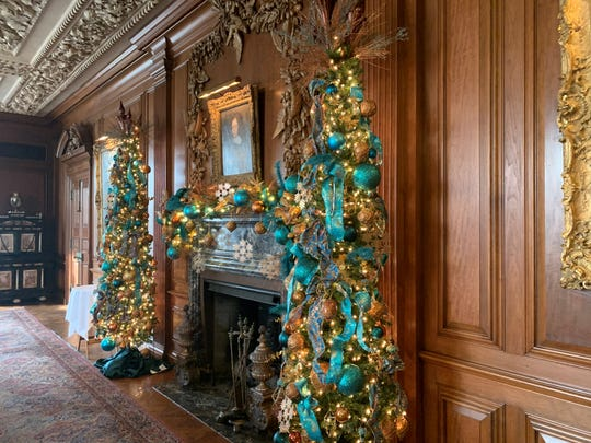 """Teal and gold ornaments add glamour to the Christmas trees and mantel in the dining room at Meadow Brook Hall. All of the decorating is done by Grand Haven floral designer Alice Waterous and her team of what she calls """"Christmas elves."""""""