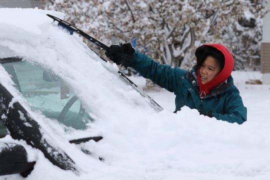 "Meg Jones cleans the snow off her car outside her house in Scottsbluff, Neb., Tuesday, Nov. 16, 2019. ""I'm glad we don't have school,"" the Scottsbluff High School junior said."