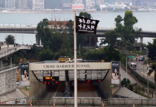 "A flag reading ""Liberate Hong Kong, Revolution of Our Times"" flies from a flagpole at Hong Kong Polytechnic University near the Cross-Harbour Tunnel in Hong Kong."