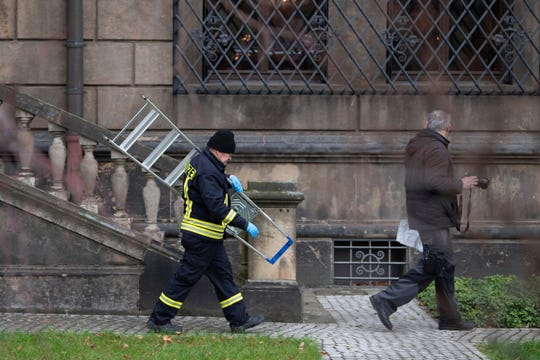 Police investigators walk in front of latticed windows of the Green Vault at the Residenzschloss, Residence Palace, a day after thieves broke into the Green Vault, one of the world's oldest museums, in Dresden, Germany.