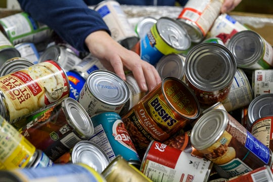 Stacia Miller, a volunteer from Hillard Lyons, a Baird company, helps sort canned goods into smaller boxes labeled for fruits, soups and vegetables inside the Victor St. Hiller building at Tri-State Food Bank in Evansville, Tuesday morning, Nov. 26, 2019. The flood of holiday donations will be packaged up and used by the food bank year-round.