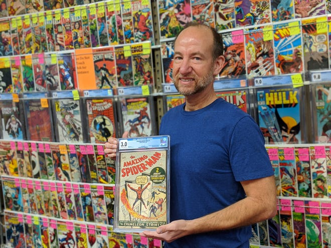 "Chris Rupp, owner of Rupp's Comics, 335 N. Ohio Ave., poses with his newest ""key book,"" ""Amazing Spider-man #1."""