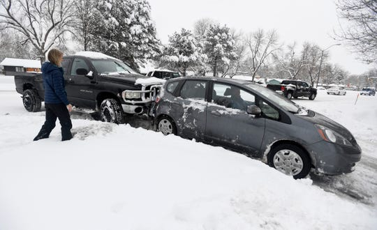 A man uses his pickup truck to push a woman's car free after it became stuck as she entered a parking lot along South College Avenue in Fort Collins, Colo. on Tuesday, Nov. 26, 2019.