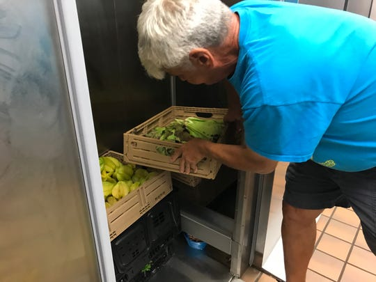 Alvin Piotter, the teacher behind the expansive gardening project at Trafalgar Middle School, checks out the day's harvest that has been brought to the school's kitchen. Included in the bins are starfruit, lettuces and an assortment of peppers.