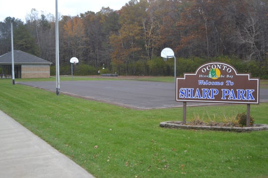 The recently resurfaced  basketball/pickleball court is seen behind the sign for Sharp Park in Oconto. In the background is a newly constructed tennis court. Both projects were done thanks to $26,500 in grants from the Bond Foundation.