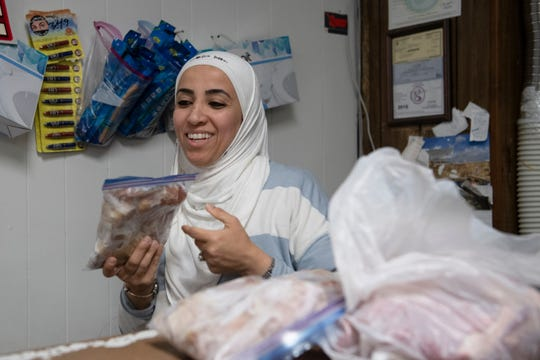 Rima Hafi rings up a customer at HolyLand International Grocery and Halal Meat Monday, Nov. 25, 2019.