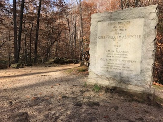 A historic marker sits in front of Poinsett Bridge, thought to be the state's oldest standing bridge.