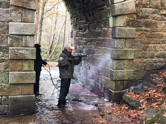 Abel Tobias, left, and Brian Long use a power washer to clean graffiti off of Poinsett Bridge in Greenville County.