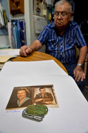 Marty Martinez looks over dog tags that belonged to Howard Connell, who served at the air base in Great Falls in the 1940s and married Josephine Patricia Kutros of Great Falls, left, in 1943. Martinez sent the dog tags and other belongings relating to Connell's family in Washington recently. The tags were found in a box of items that were purchased at a garage sale in Great Falls.