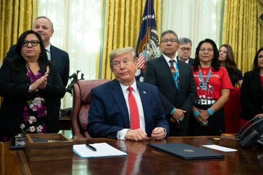 President Donald Trump listens to a question during an event to sign an executive order establishing the Task Force on Missing and Murdered American Indians and Alaska Natives in the Oval Office of the White House on Tuesday.