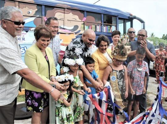 Guam Gov. Lou Leon Guerrero and Lt. Gov. Joshua Tenorio have a lot of help cutting the ribbon to launch the island's newest bookmobile as part of 70th anniversary of the library Nov. 26, 2019.