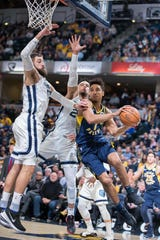 Nov 25, 2019; Indianapolis, IN, USA; Indiana Pacers guard Malcolm Brogdon (7) passes the ball while Memphis Grizzlies center Jonas Valanciunas (17) and guard Dillon Brooks (24) defend in the first half at Bankers Life Fieldhouse.