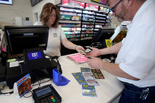 Ralph Cox buys scratch-off tickets at the Stop-and-Geaux gas station on Highway 59 in Gulfport, Miss., Monday, Nov. 25, 2019. People across Mississippi got into the scratch-off fever Monday as lottery tickets went on sale for the first time in the state.