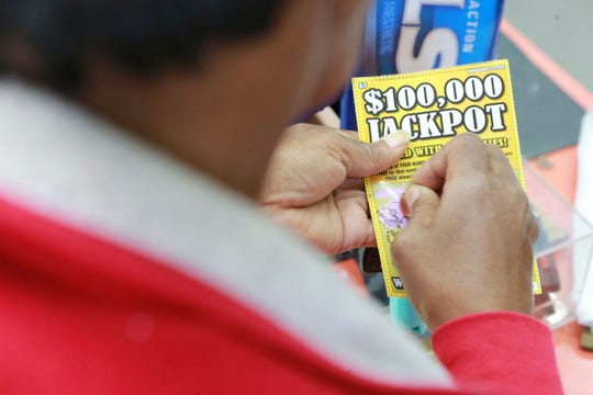 A Lee County resident takes a moment and scratches off her first lottery ticket in Tupelo, Miss., Monday, Nov. 25, 2019, as the new statewide lottery begins.