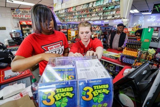 Wakendra Johnson, left, and Elizabeth Bryant pull tickets for customers Monday, Nov. 25, 2019, at the Shell station in Meridian, Miss. People across Mississippi got into the scratch-off fever Monday as lottery tickets went on sale for the first time in the state.