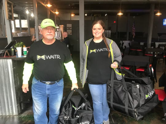 Roger Fowler and Kelsey Lee take delivery bags out of Baker Brothers on Tuesday for deliver for free Thanksgiving meals from Waitr.