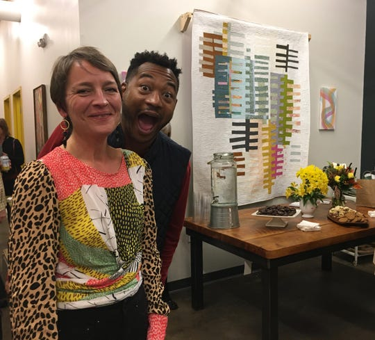 "Megan Stair on Nov. 22 with pal Pee Jay Alexander in front of a fabric work by Melissa Everett. ""That piece sold that night,"" says Stair."